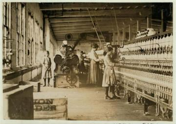 Young girls work in the spinning area of a textile mill.